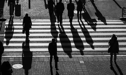 silhouette people walking on pedestrian crosswalk at the junction