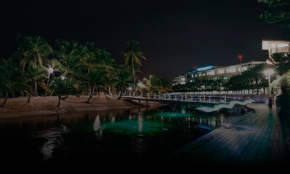 Camana Bay at nighttime with a modern waterfront town by the Caribbean sea