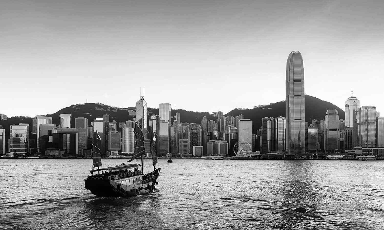scenic view with tourist sailboat crosses victoria harbor from Kowloon side to the hong kong island
