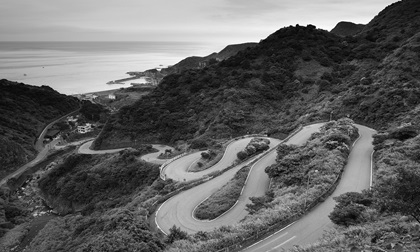 A curvy road through the grassy hills with a view of the ocean, black and white.