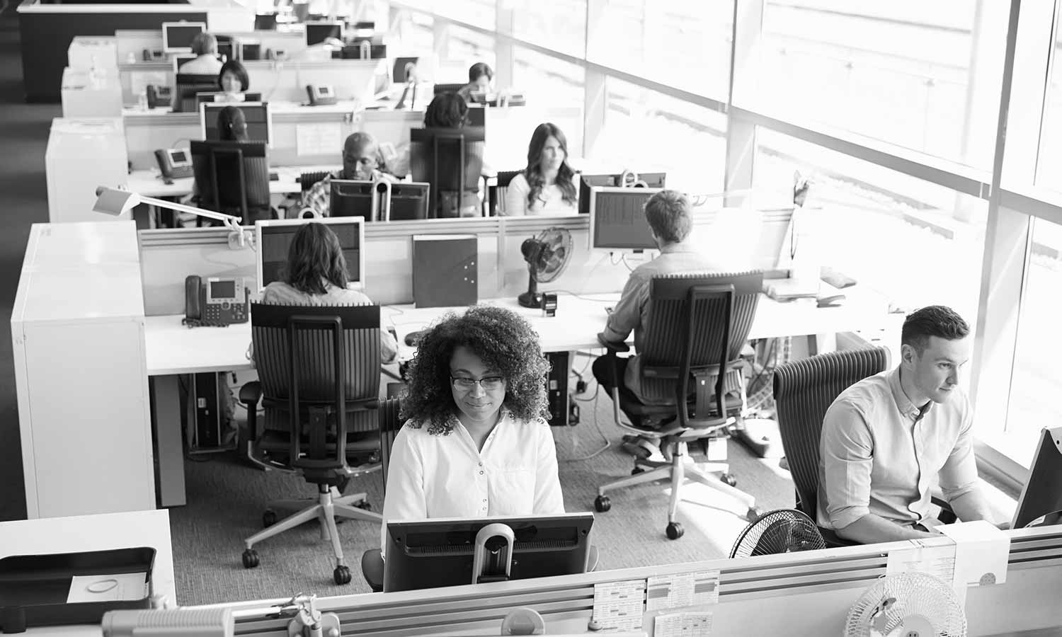 Busy office with rows of desks, black and white