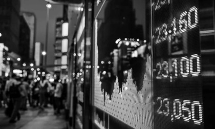 display of stock market quotes with city scene reflect on glass