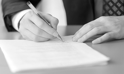Male hand with pen signing document, black and white