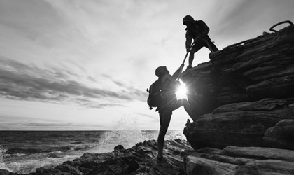 Climber giving companion a helping hand, strength, support, weakness concept, black and white with ocean in background.