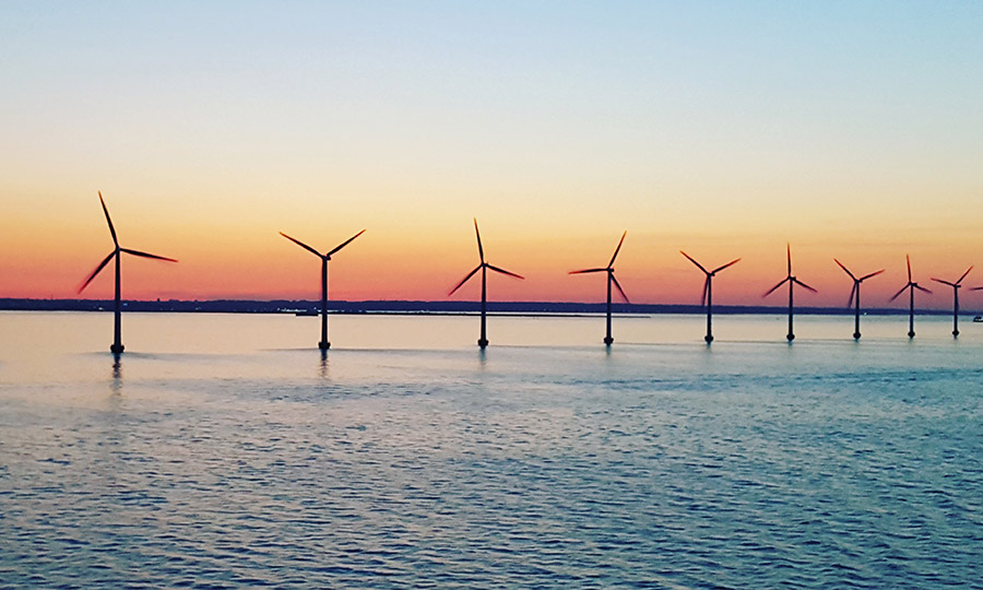 Wind turbine in the middle of sea with a beautiful sunset