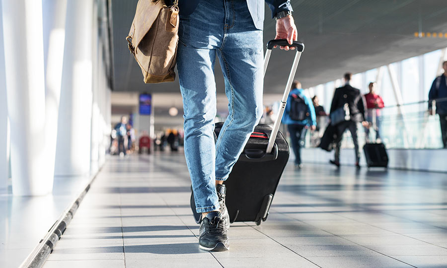 Man in airport terminal walking with shoulder bag and luggage