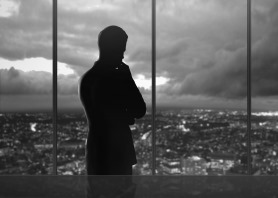 Businessman thinking in front of skyline
