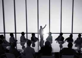 Silhouette of a business meeting in front of floor-to-ceiling glass
